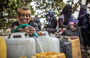 Suad pours water from a hose into a yellow water container