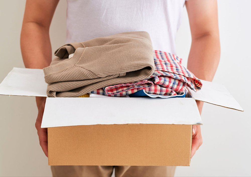 A pair of hands holding a cardboard box full of clothes
