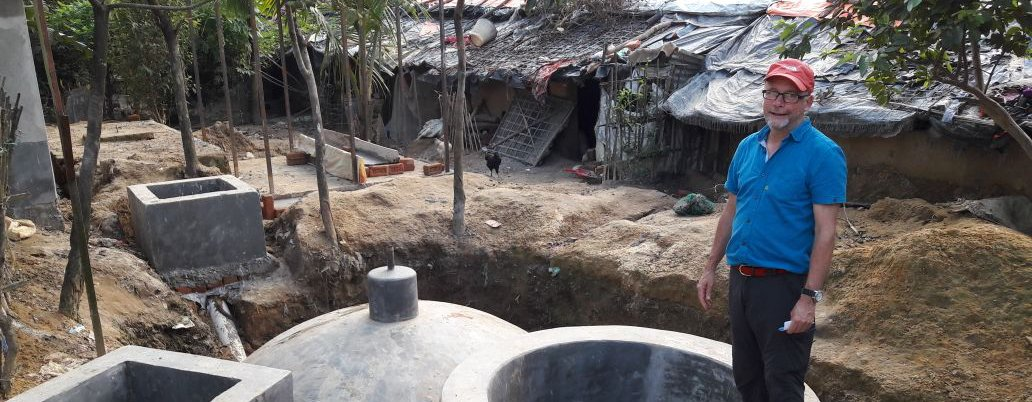 Andy stands by a biogas unit in a refugee camp in Bangladesh