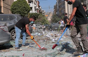 A few people wearing surgical masks sweep the rubble from the streets