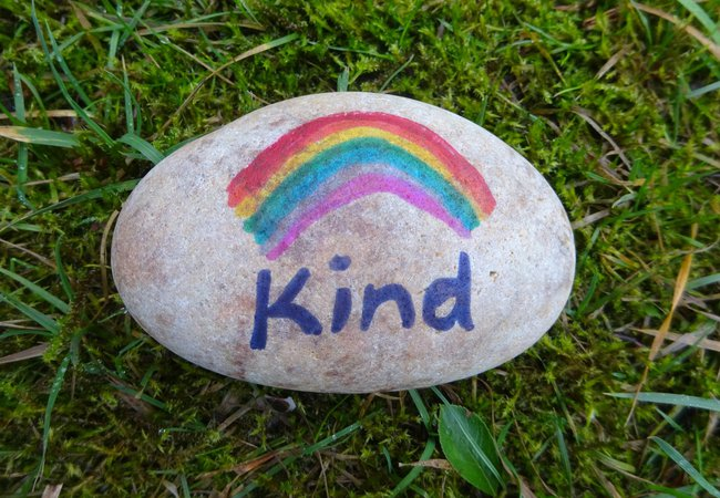 A pebble painted with a rainbow and the word 'Kind'.