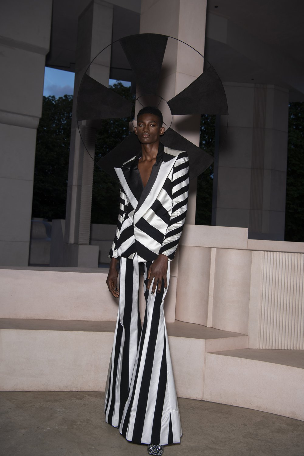 A model wears a black and white wide-striped satin suit made from pre loved Oxfam bridal wear and a black halo
