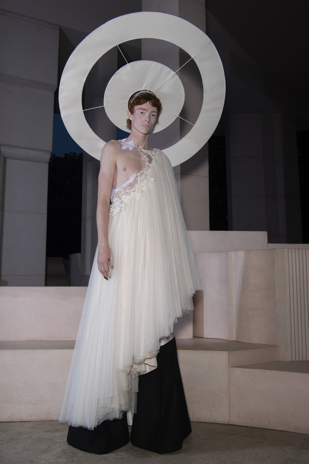 A model wears a demi-couture bridal lace toga made from Oxfam pre-loved bridal wear over black flares and a white halo.