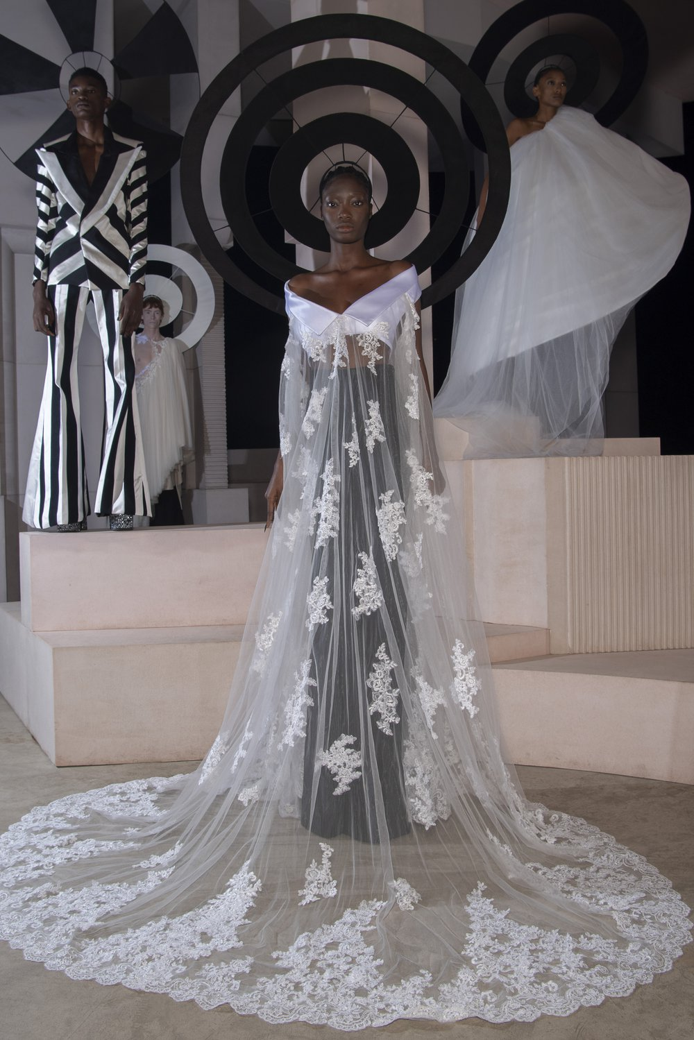 A model wears a demi-couture bridal gown made from Oxfam pre-loved bridal wear and flared suit trousers. Models stand in the background wearing other looks