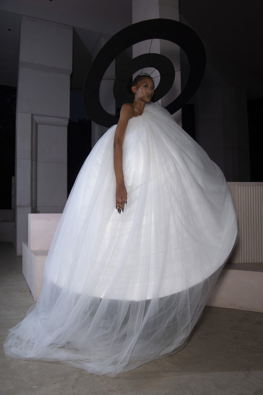 A model wears a demi-couture bridal gown made from Oxfam pre-loved bridal wear and a black halo.