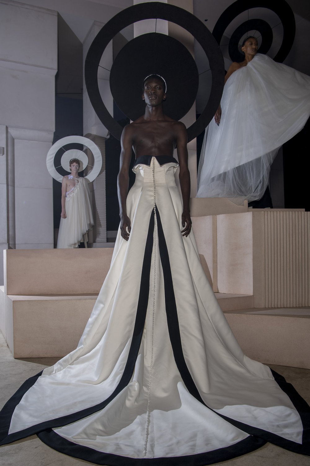 A model wears a demi-couture satin bridal gown made from Oxfam pre-loved bridal wear and suits with black edging and a black halo. The dress echoes Chanel