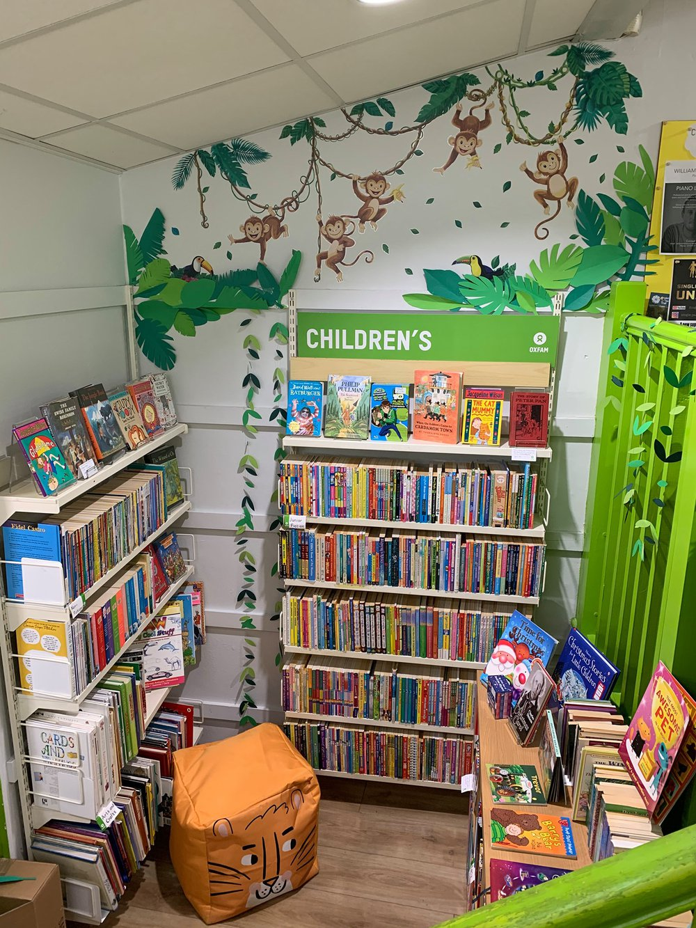 Oxfam Preston's children's books section with new monkey mural on the wall and a toget foot cushion on the floor
