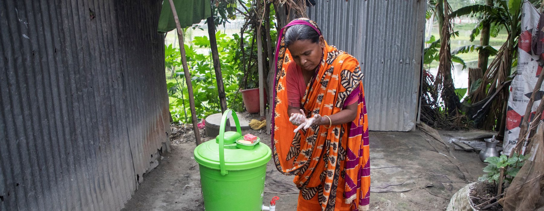Mosammat Rabeya Begum washes her hands at an outdoor tap