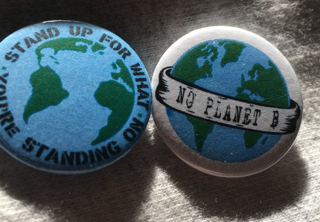 Two badges, one says 'stand up for what you're standing on' and the other says 'no planet b'