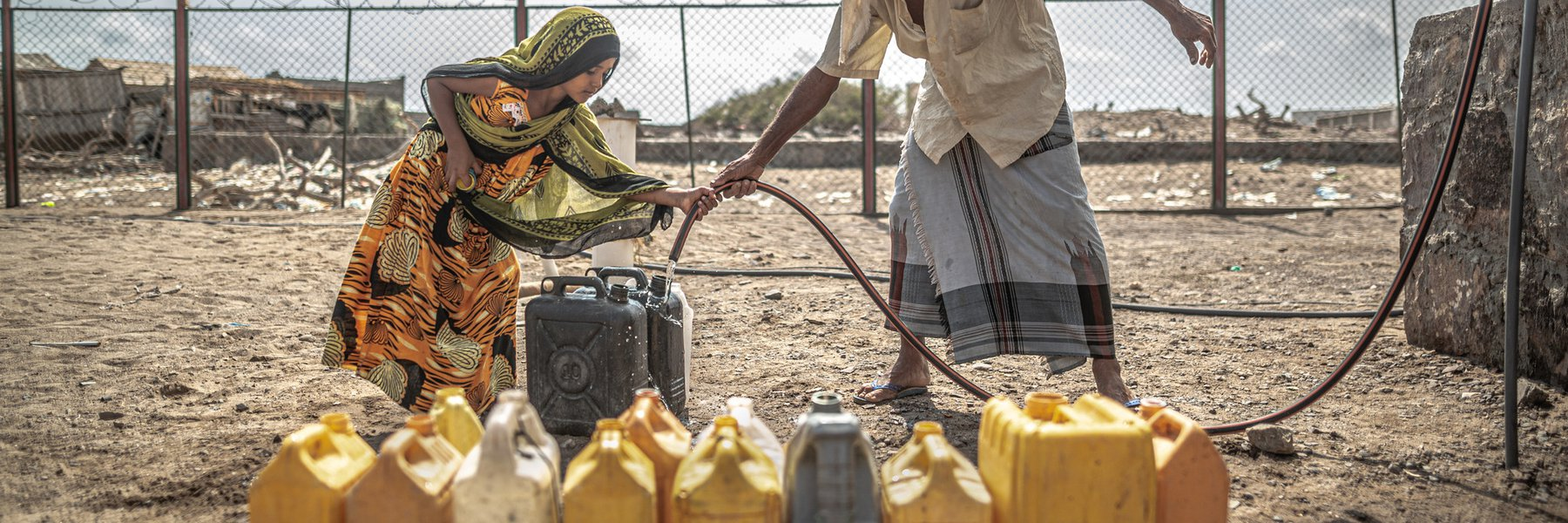 Naaser Mohamed Fakih and his granddaughter fill water containers with water