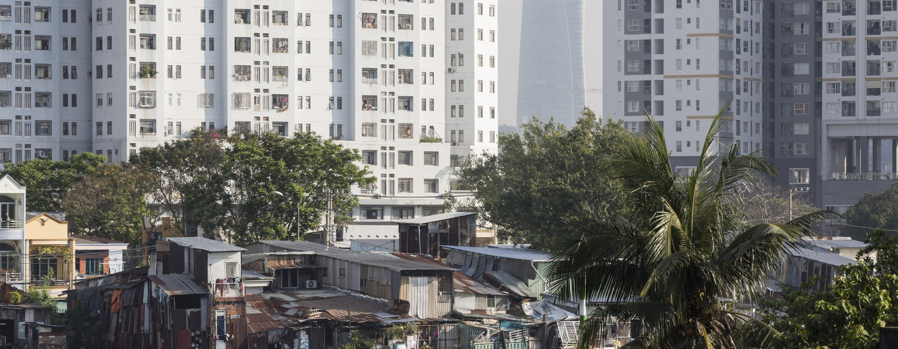 Large expensive skyscrapers rise above slums along the river