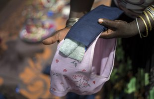 A pair of hands place a black reusable sanitary towel on a pair of light pink knickers to demonstrate how they work