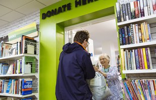 A man donates a bag of goods to his local Oxfam shop