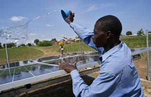 Joshua throws water over the community solar panels to clean them