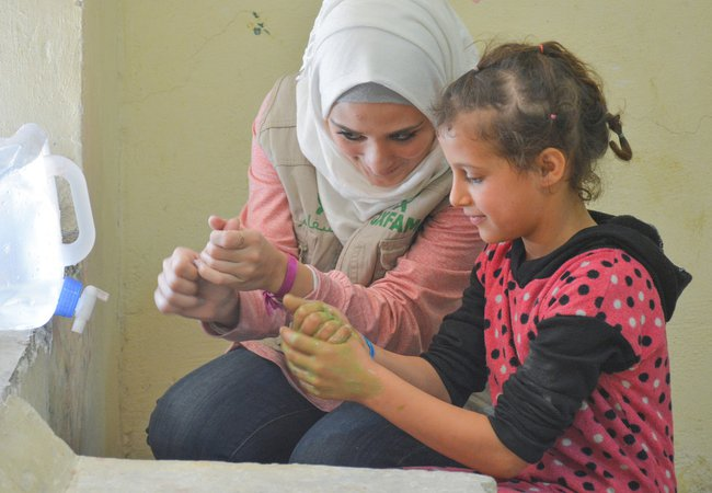 Sana, an Oxfam volunteer in Aleppo, shows children from Aleppo how to wash their hands properly.