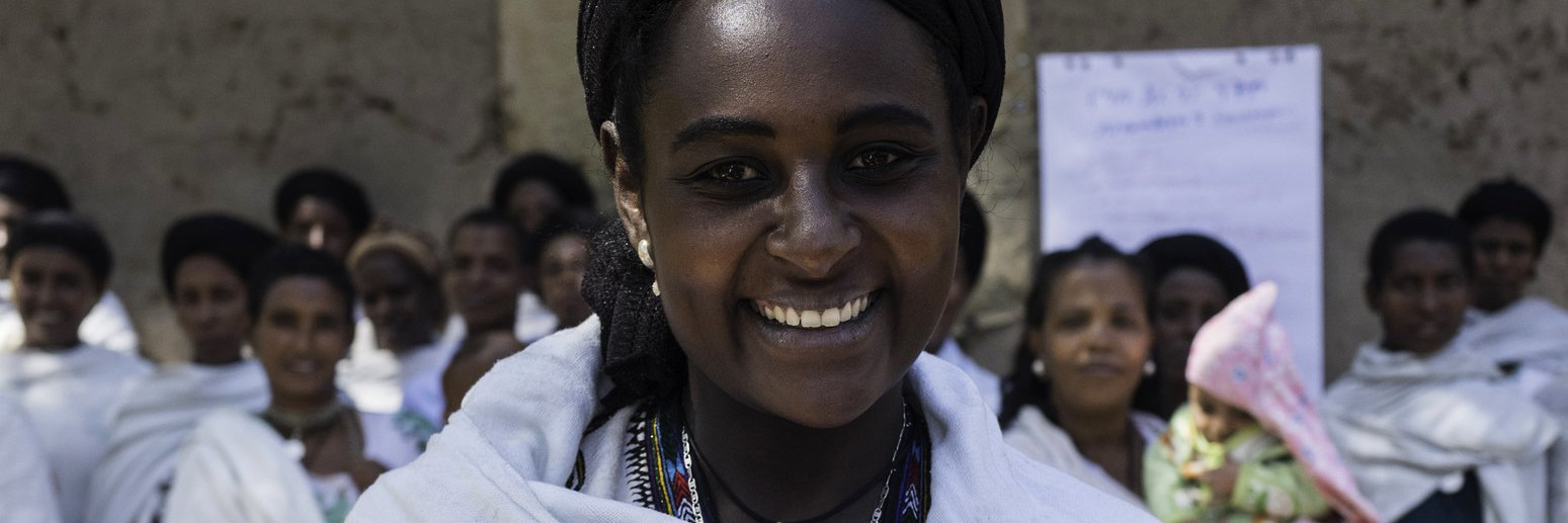 Addise wears a white robe and black headwrap and is smiling. She holds books with one arm.