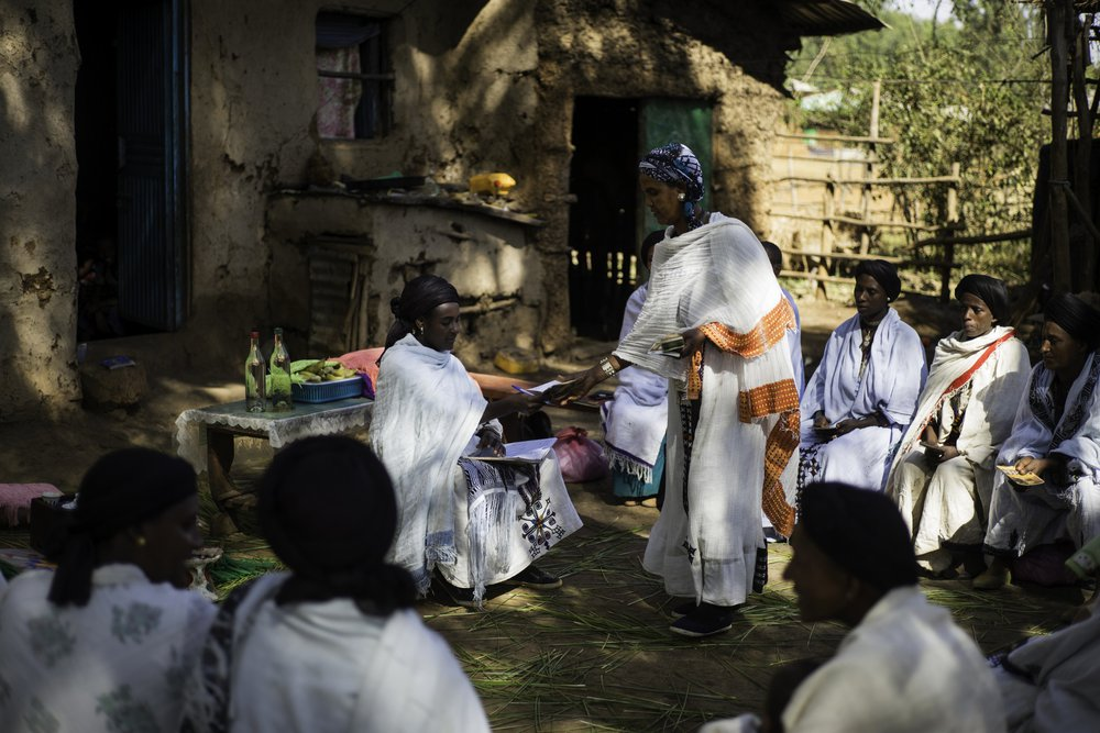 The women in the beekeeping cooperative sit around Addise outside in front of a paper presentation board