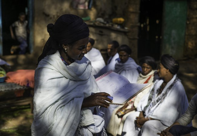 Addise stands holding an open notebook surrounded by women from the honey coop. They all wear white robes and have black headwraps on.