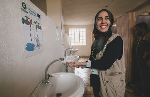 An Oxfam worker washes her hands in Oxfam installed sinks in a school bathroom
