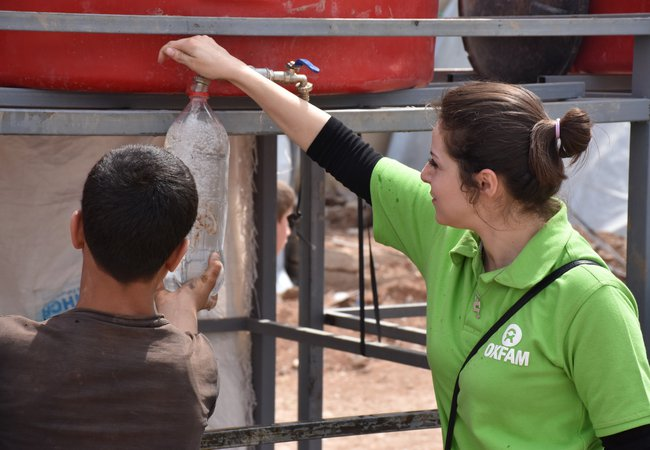 An Oxfam staff member helps a child fill a water bottle from a tank in Herjalleh collective shelter.