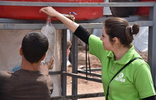 A humanitarian worker in  agreen Oxfam shirt fills up a water bottle from a tap in a tank for a boy