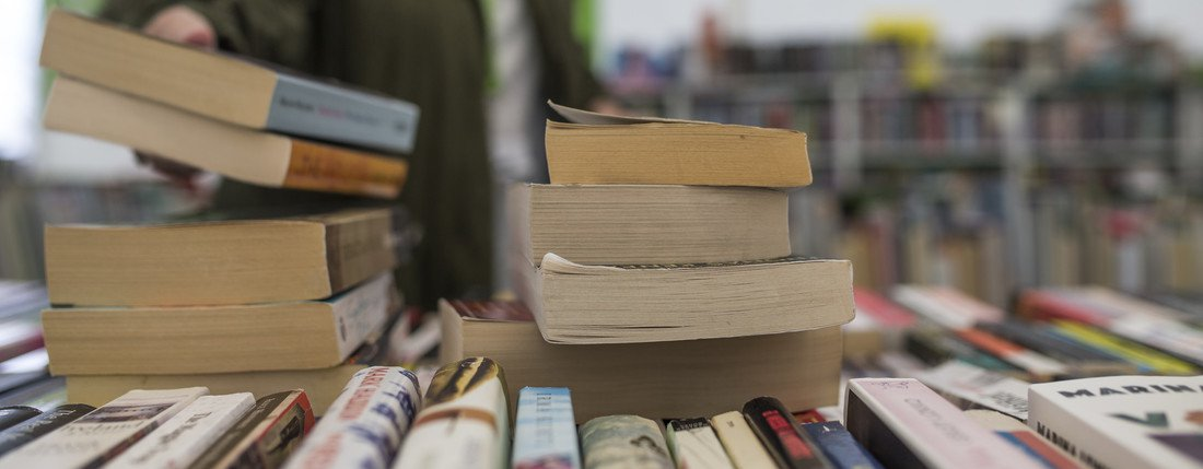Someone reaches for a stack of books on a display