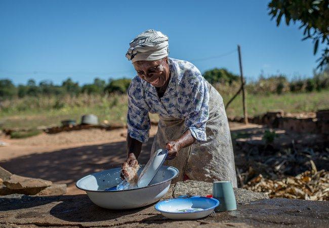 Emmily washes dishes in Zimbabwe