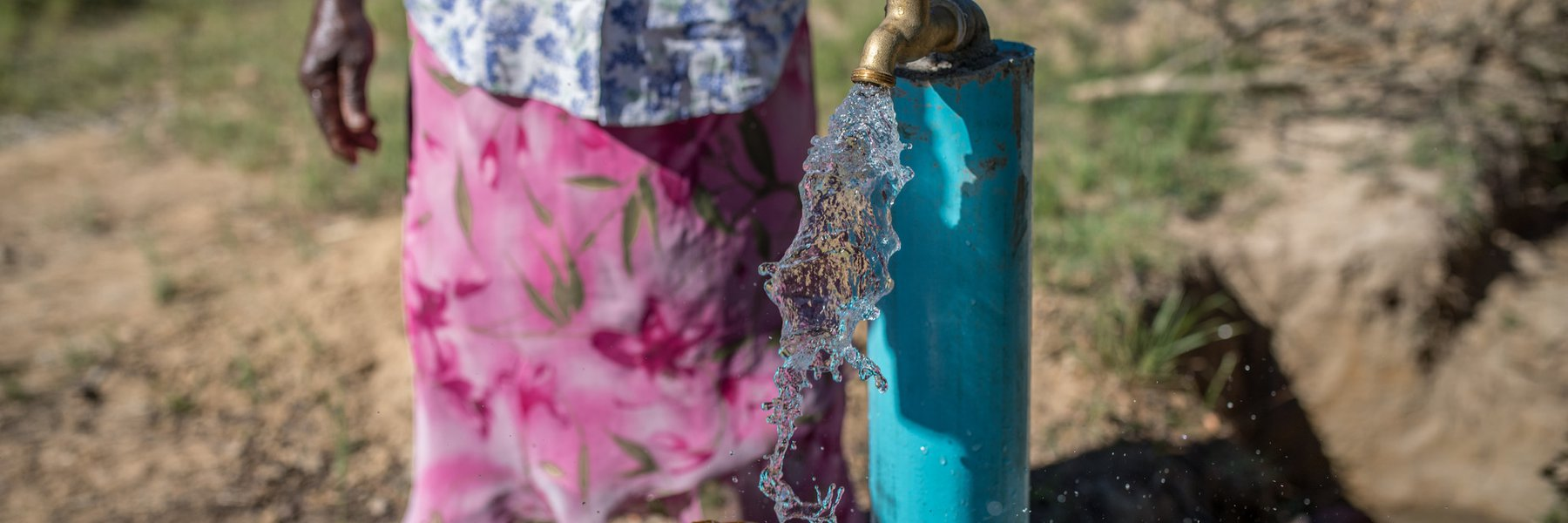 Water flows from a tap into a yellow water container. Emmely stands in the background.