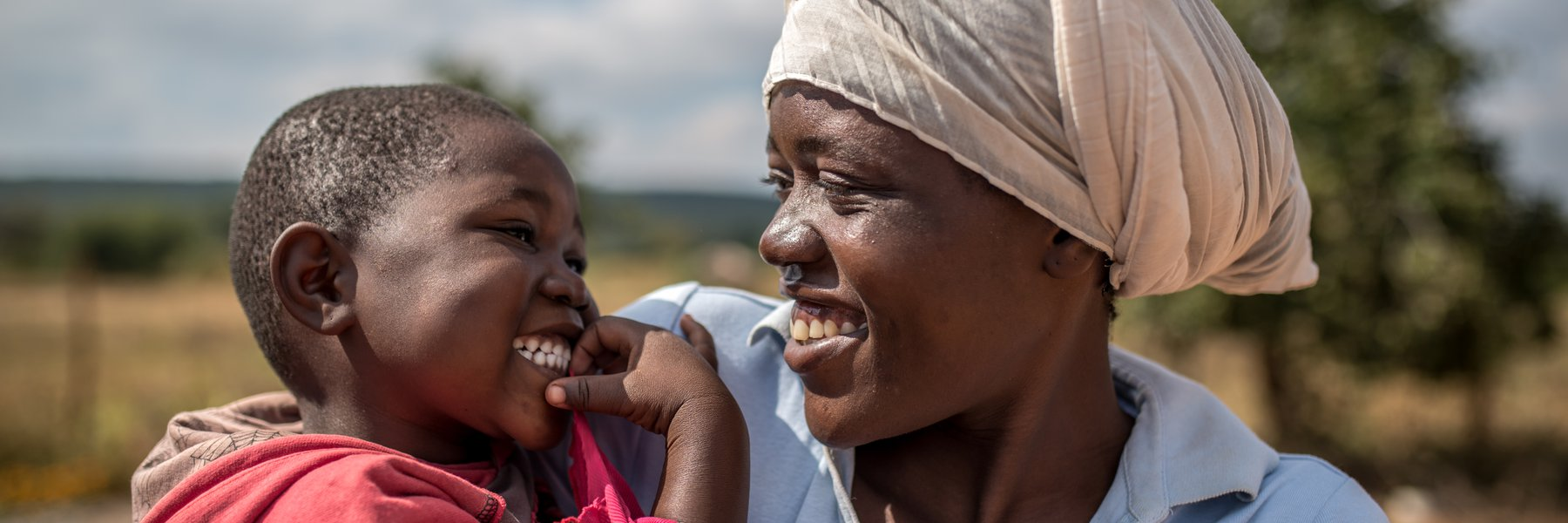 Sibongisiwe, 25, stands with her little girl Charity*, 3yrs, outside the family home in Bubi District, Ward 23, Zimbabwe.
