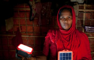 Rohingya refugee Asia Bibi* with solar powered lamp provided by Oxfam