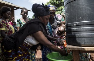 A woman wearing a black headwrap washes her hands at a metal Oxfam handwashing point with people in the background