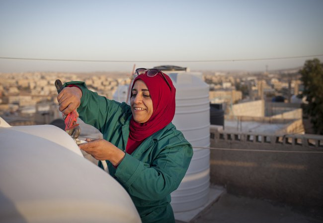 Mariam, a woman aged 44, is fixing the water tank on the rooftop of her house in the town of Zarqa in Jordan.