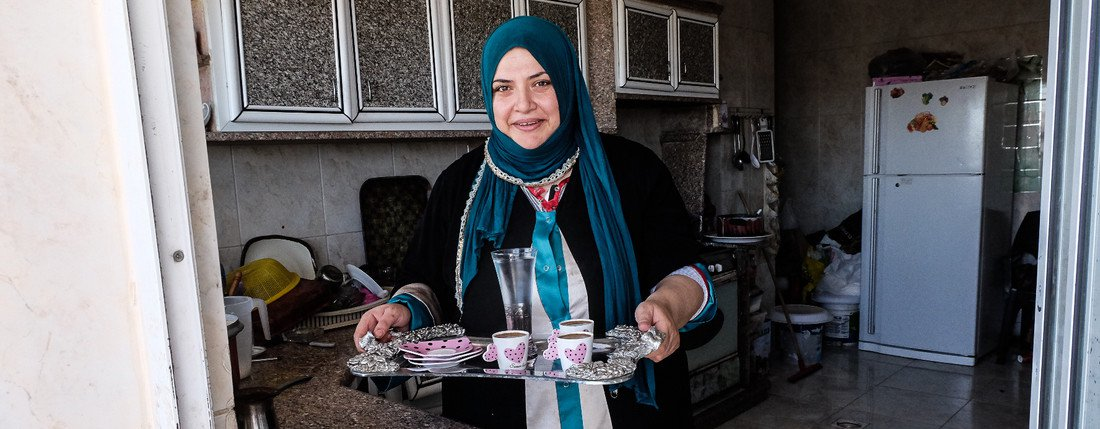 Huda carrying a tea tray at home in Jordan