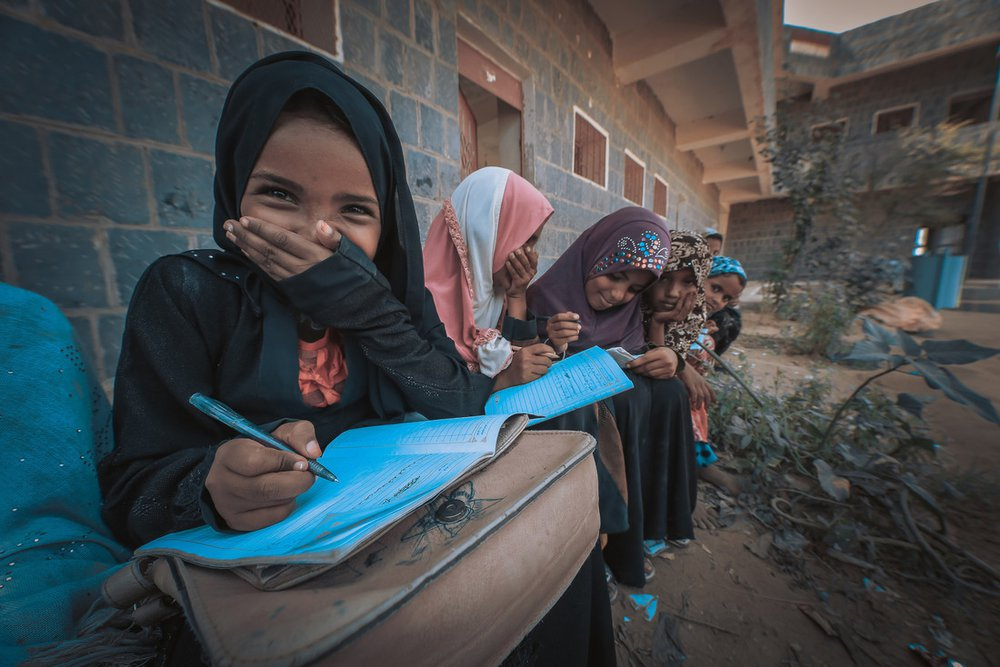 A group of young girls sit studying outside a school in Yemen.