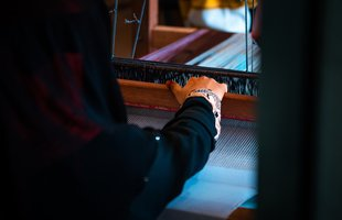 A woman's hand is on a weaving machine