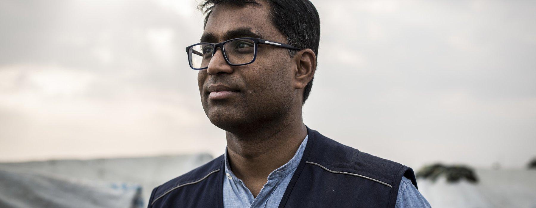 A portrait of Dhananjayan Sriskandarajah wearing a black Oxfam vest.