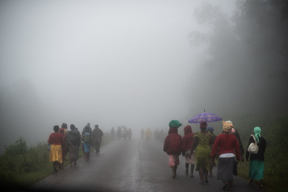 People walk along a road in the rain towards a food distribution point in Zimbabwe after Cyclone Idai caused heavy rains, flooding and landslides in 2019.