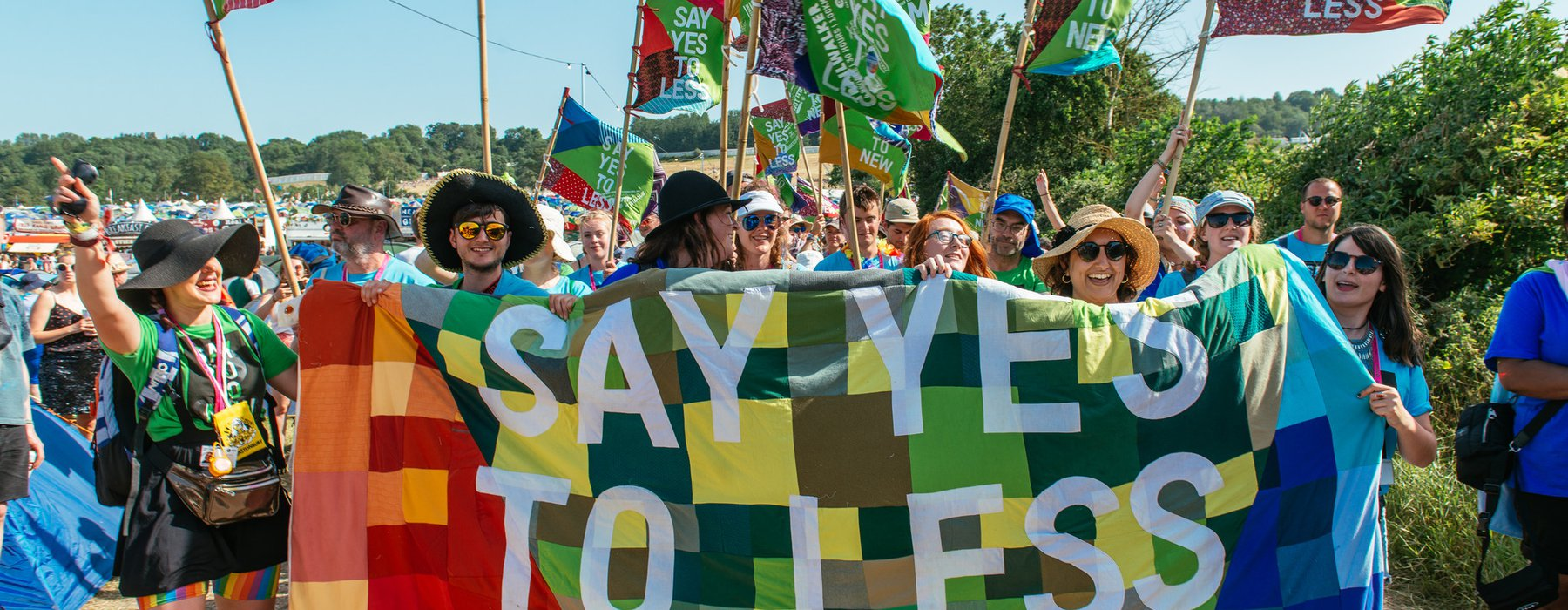 A group of volunteers stand by a patchwork banner that says 'say yes to less'