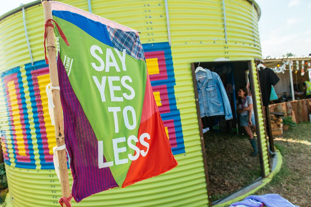 A patchwork say yes to less banner flies in front of a pained Oxfam water tank at a festival