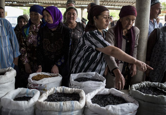Women at a market look at large bags filled with raisins