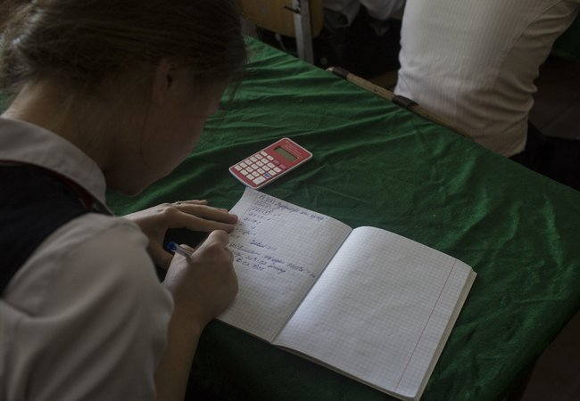 A school girl in Tajikistan is doing some algebra in her class.