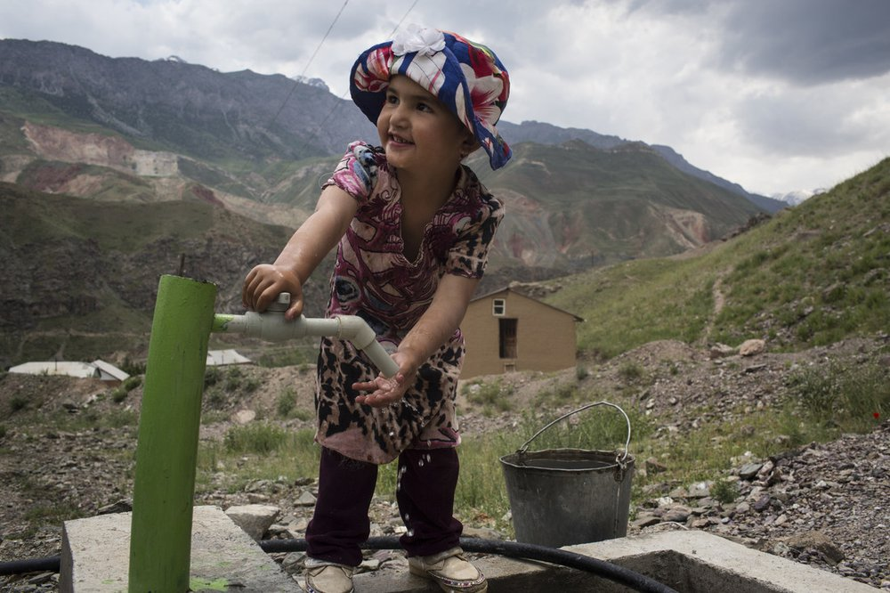 A four year old girl fills a bucket with water from an clean water tap next to her home in Tajikistan.