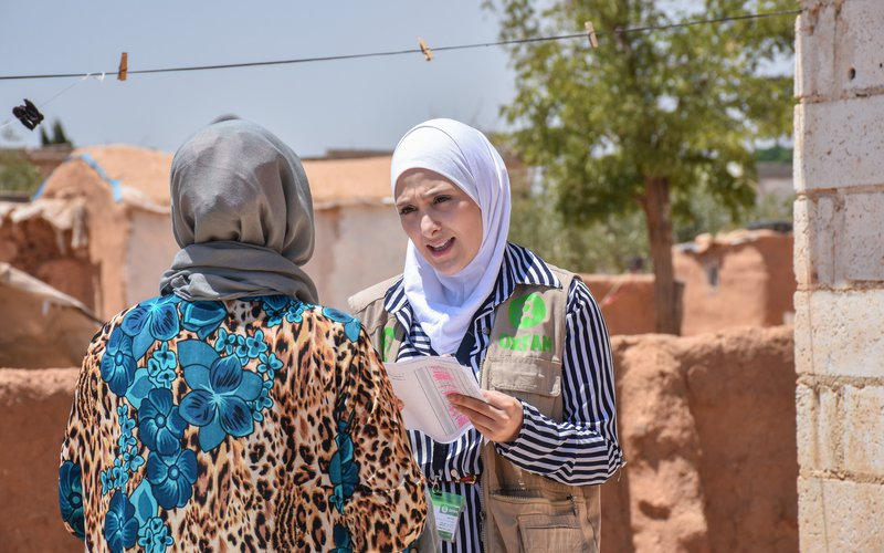 Sana wears a white hijab and Oxfam vest as she talks with a person in Rural Aleppo.