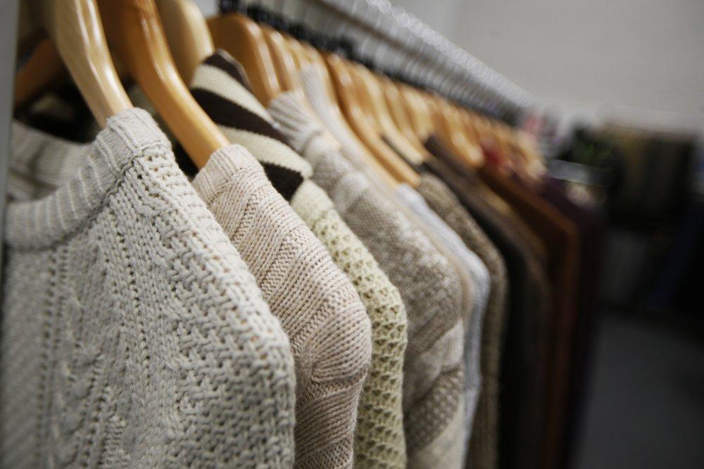 Grey knitwear on a clothes rail
