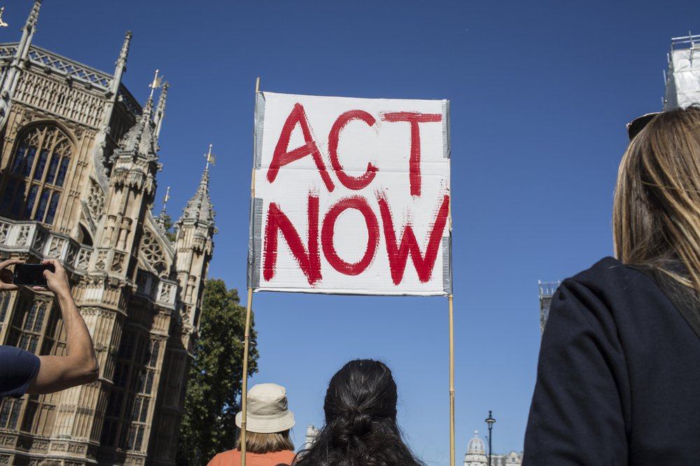 A banner on a London climate march that says 'act now' in red paint