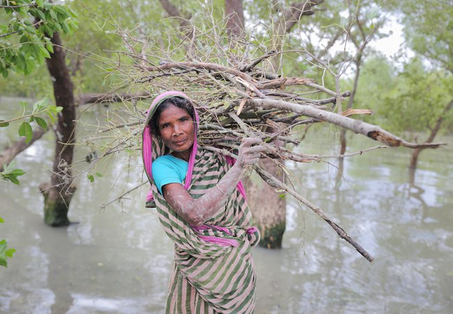 Nurjahan stands in floodwater with a bundle of sticks on her back and mud on her hands and smiles