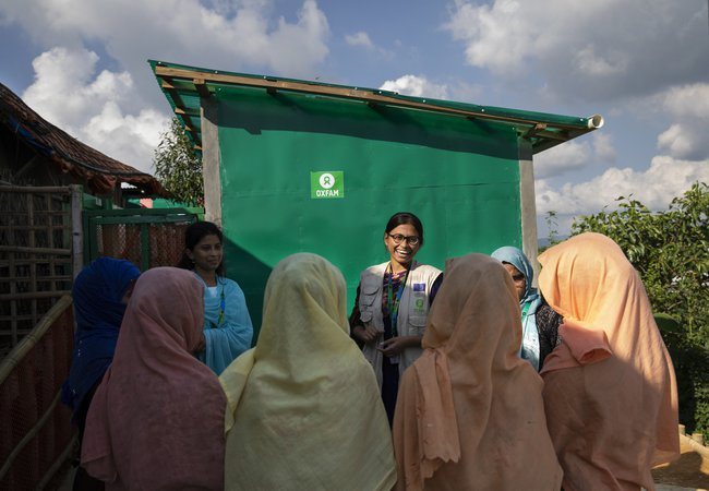 Oxfam staff member Iffat talks with a group of women wearing pastel-coloured headscarves about the toilets in the background