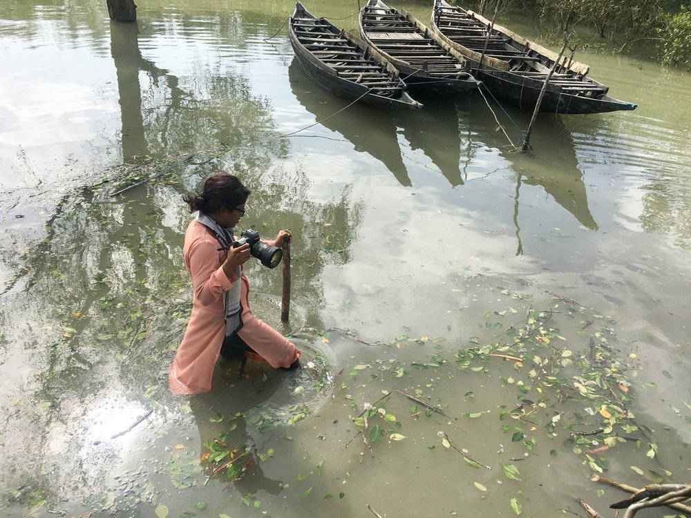 Fabeha Monir wades through floodwater in Bangladesh holding a camera