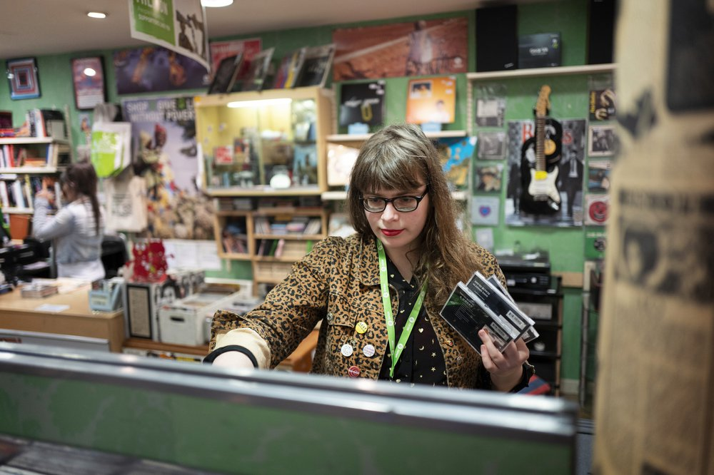 Music shop volunteer, Lucy, arranges CD display in Oxfam music shop, Byres Road, Glasgow