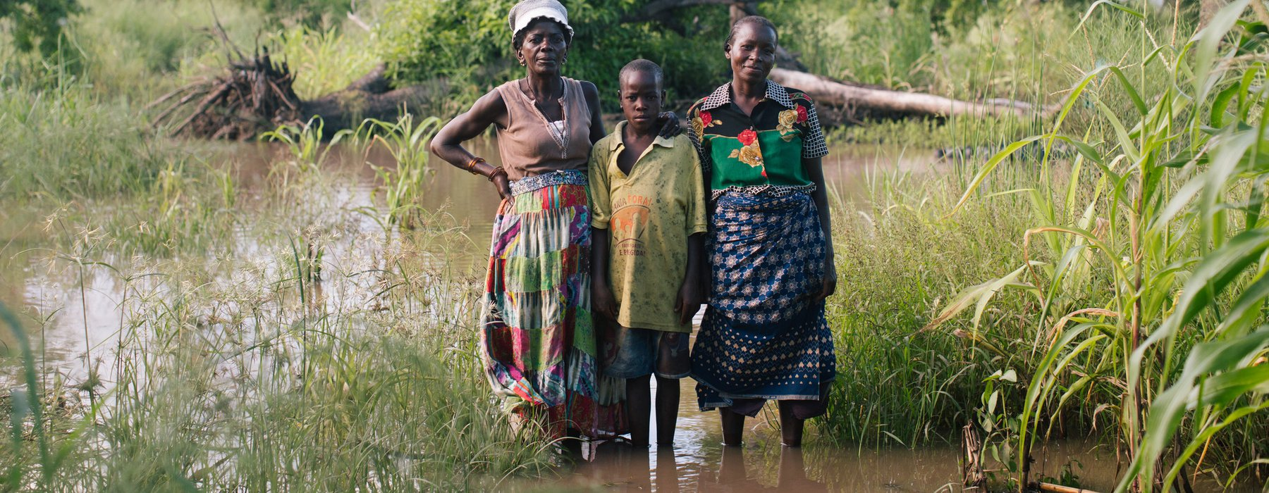 Fatima, Rita and a child stand in a flooded area.